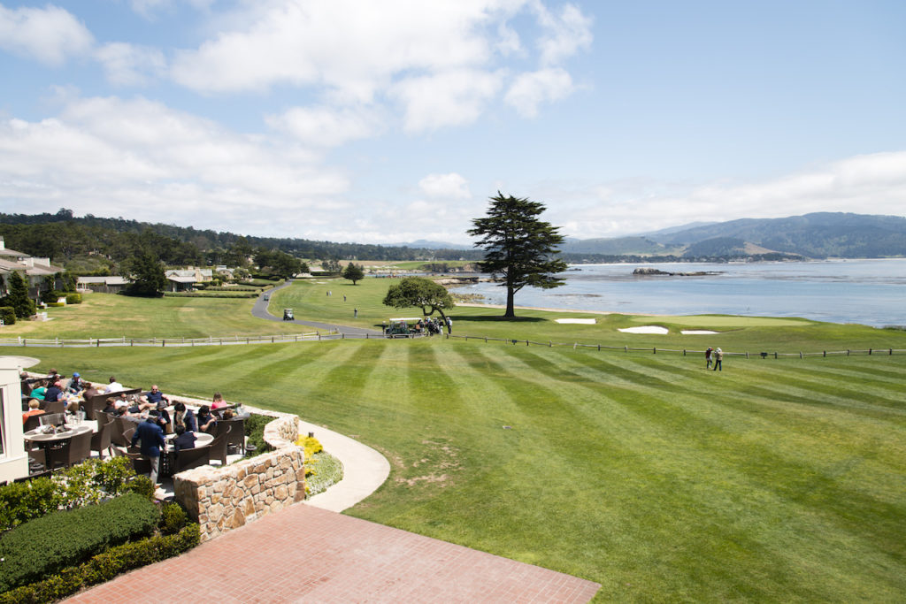 A view of the outside restaurant, green grass of the gold course and the blue ocean, Pebble Beach CA.