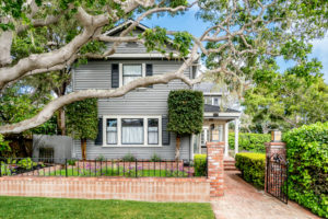 Blue historic craftsman home with brick wall and oak tree in Pacific Grove, CA